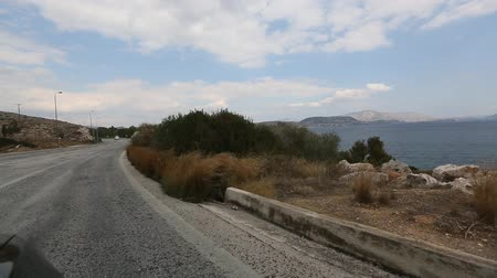 Driving on the car along the road in Athens along the Aegean Sea.