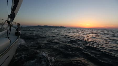 Sailing in the wind through the waves during sunset. Boat shot in full HD at Aegean Sea. Cruise luxury yachting.
