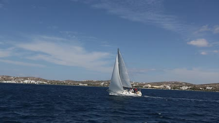 Yacht with white sail glides on the sea surface.