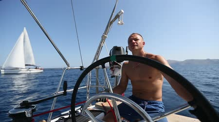 Young man skipper steers boat sailing during yacht regatta.