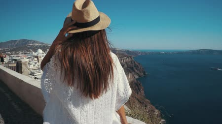 УВР : Young sexy woman is on the greek island Santorini in a white dress and and straw hat white greek houses volcano sea sunny weather