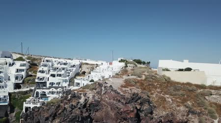 УВР : Santorini aerial view video of greek island with white houses and blue roofs on sunset and in the daylight on volcano and sea around the island, aero