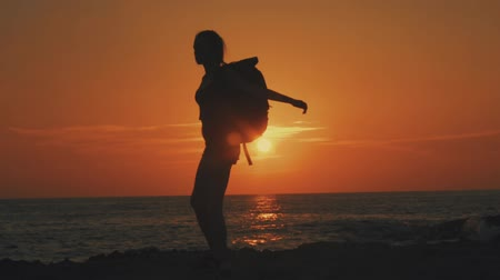goes : Yong sexy woman girl with backpack and straw hat is turning around counterclockwise at sunset or at dawn in Cyprus on the beach near the sea, in the distance one sees the horizon and the orange sun, Silhouette of a girl, slow motion video, 100 frames per