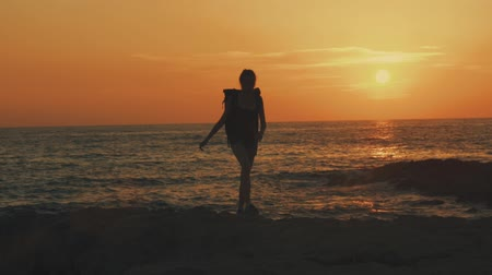 ás : A young woman with a backpack in Cyprus is walking along the beach at sunset or sunrise against the background of orange sun and sea, sun glare, Silhouette of a girl, slow motion video, 100 frames per second. Stock Footage