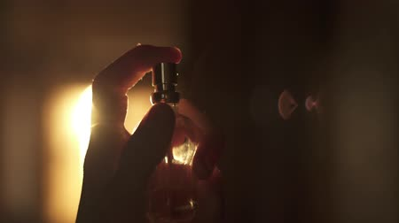 Young woman squirting perfume on her neck. In a room orange sunset light. Splashes fly slowly in the sunlight. Stok Video