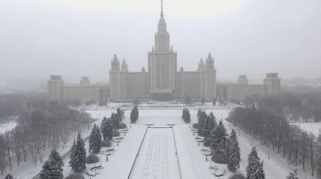 moskova : Drone goes up and shooting Moscow State university and red ballon in form of heart flying up. It is snowing. Winter. There are trees under the snow near the university. Stok Video