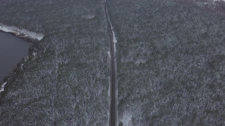 télen : Aerial footage of road between trees in winter snowy forest near lake in Russia. Car driving on the road. Stock mozgókép