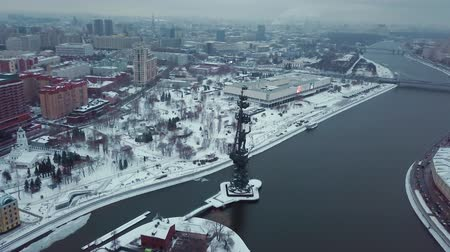 látnivalók : Drone flies over the Moscow River around the monument of Peter the Great. All buildings in the snow. Red October and Central House of Artists in shot. Winter. Overcast weather. Stock mozgókép