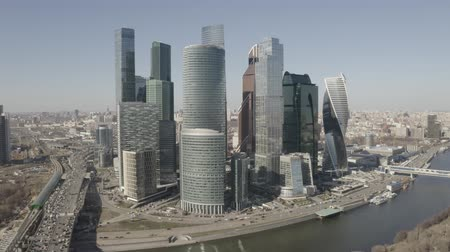 auto parking : Aerial view on Moscow city skyscrapers and Moscow river. Sunny, blue sky, spring. Cars driving on the motorway. Stock Footage