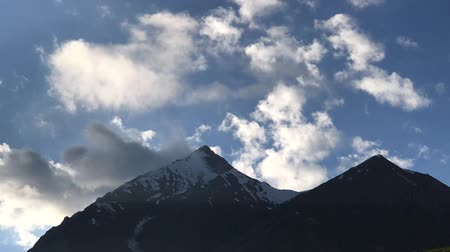 armenia : Timelapse ?f clouds flowing across the blue sky over the snowy tops of the mountains, Georgia, Caucasus. Mountain valley, nature of Georgia, Kazbegi. Clouds in rocky mountains.