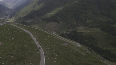 serpentine : Aerial view of Furka Pass winding road with driving cars in Swiss mountains. Beautiful nature, green fields, hills and lakes around. Switzerland Travel time. Stock Footage
