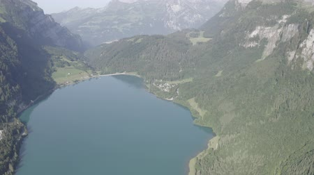 hegytömb : Aerial view footage of Klontalersee mountainous valley. Glarus Kanton, Switzerland. Beautiful Swiss nature. Hills, rocks, lake, Stock mozgókép