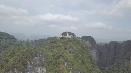 mantra : Aerial footage of Buddha on the top of Tiger Cave Temple, Wat Thum Sua, green stone rocks, mountains, Krabi, Thailand.