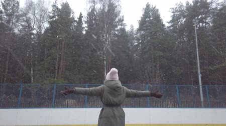 Happy young woman rejoices at the first snow, running and whirling on the sports ground, skating rink. New Year. Christmas Winter mood. Big snowflakes. Stok Video
