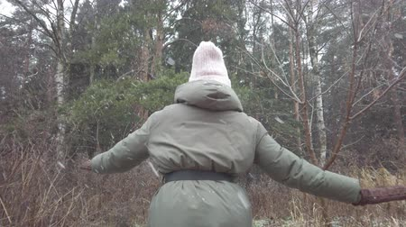 Happy young girl walking in winter forest. It is snowing. First snow. Snowflakes falling. New Year. Christmas vacation.