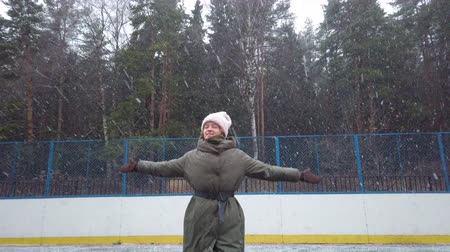 kar taneleri : Happy young woman rejoices at the first snow, running and whirling on the sports ground, skating rink. New Year. Christmas Winter mood. Big snowflakes. Stok Video