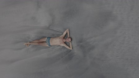Aerial footage of man lying on white and black sand Virgin beach, relaxing, waves touches his body. Drone goes up.