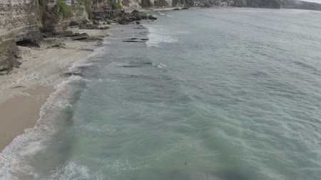 surfistas : Aerial view of Dreamland beach, waves breaking on coastline, beautiful cliff, Bali, Indonesia. Exotic nature. Tropical landscape. Archivo de Video
