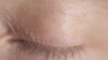 Macro close up gray blue mans eye. Man opens eye and blinking. Eyelid, eyelash, iris, face. Natural beauty.