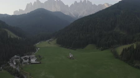 dolomit : Val di Funes, South Tyrol  Italy - 07.01.2019: Aerial footage of St Joahn church on green meadow in mountains, Santa Maddalena village, Dolomites, Val Di Funes, Italy.