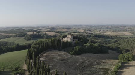 Aerial footage of a Buonconvento castle villa with cypress trees road, green hills and glades around at sunset. Val dOrcia, Tuscany, Italy Dostupné videozáznamy