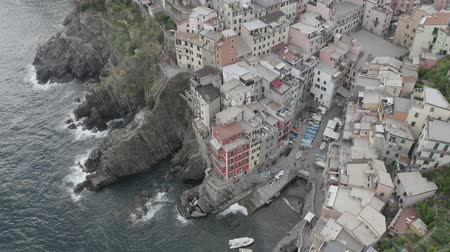 Aerial view of Riomaggiore Bay village. Colorful italian houses on rocky coast. Boats floating in the sea. Foaming waves breaking on stones. Cinque Terre, Italy.