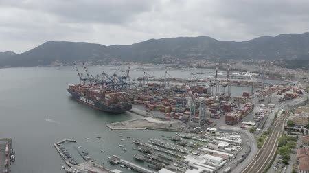 tersane : LA SPEZIA  ITALY - JULY 7, 2019: Aerial footage of Container Terminal and Cargo ship of La Spezia port. Freight containers in rows at the shipyard. Global Logistics Shipping industry. Stok Video