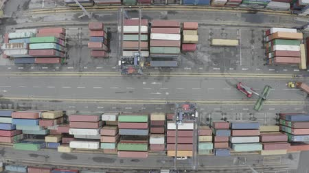 造船所 : LA SPEZIA  ITALY - JULY 7, 2019: Aerial footage of Reach Stackers move containers at a freight terminal. Forklifts unload the ship. Sea container terminal. Storage containers area.