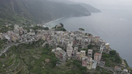 Aerial footage of Corniglia village on rocky coast. Colorful italian houses, church, green mountains and blue sea. Cinque Terre, Italy. Dostupné videozáznamy