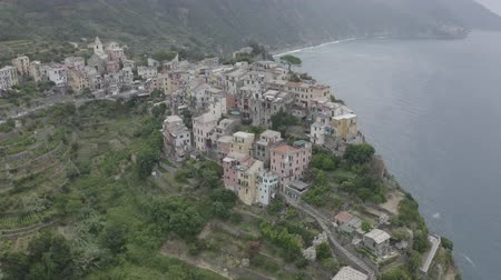 Aerial footage of Corniglia village on rocky coast. Colorful italian houses, church, green mountains and blue sea. Cinque Terre, Italy. Stok Video