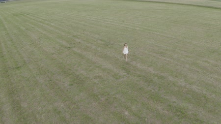 farmhouse : Aerial footage of young brunette girl with long hair in white dress runs in a large empty field with open hands. Drone flying after the woman. On the background village houses. Stock Footage