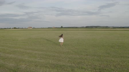 Aerial shot of young brunette woman with long hair in a white short dress is whirling with open hands in large empty field. Drone flies around a girl. On the background village houses. Stok Video