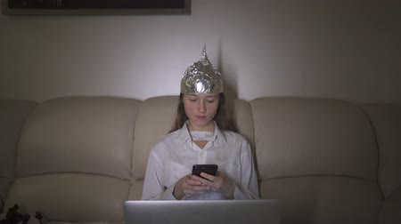 Tin Foil Hat protects woman`s brain from 5G waves, electromagnetic fields, mind control. Girl typing message in mobile phone.