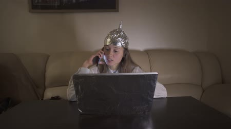 Young woman in Tin Foil Hat speaks expressively on the phone, waving hands. Foil hat protects her from 5G waves, electromagnetic fields, mind control, mind reading, global conspiracy