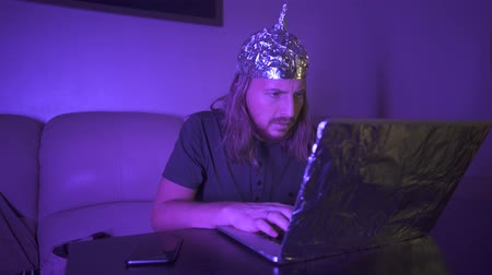 Man with long hair in Tin Foil Hat type message on phone, work at laptop. Man tired of computer, rubbing eyes. Foil hat shields him from 5G waves, electromagnetic fields, mind control, mind reading.