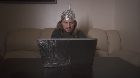 Exhausted man put on aluminum foil hat on head and search in internet information about conspiracy, type text on laptop. Foil hat shields him from 5G waves, mind control, mind reading, illuminati.