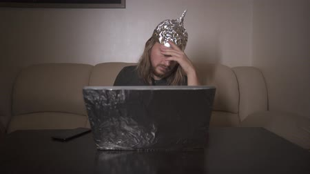 Man with long hair in Tin Foil Hat type message on phone, work at laptop. Man tired of computer, ribbing eyes. Foil hat shields him from 5G waves, electromagnetic fields, mind control, mind reading. Stok Video