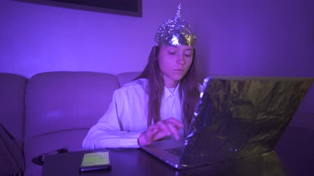 Young woman in Tin Foil Hat typing text on keyboard, laptop with foil, then take mobile phone. Foil hat shields her from 5G waves, electromagnetic fields, mind control, mind reading, global conspiracy, illuminati.