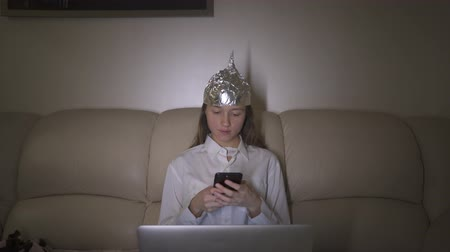 оборонительный : Tin Foil Hat protects woman`s brain from 5G waves, electromagnetic fields, mind control. Girl typing message in mobile phone.