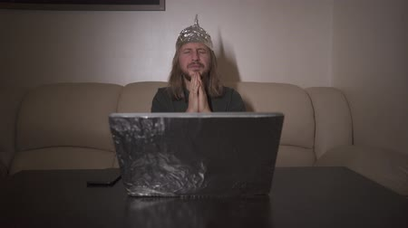 век : Man with long hair in Tin Foil Hat is tired of computer, rub and screw up eyes. Foil hat protects him from 5G waves, electromagnetic fields, mind control, mind reading, global conspiracy, illuminati. Стоковые видеозаписи