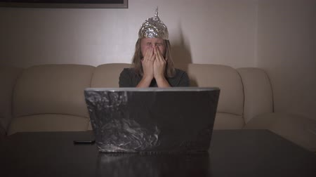 ón : Man with long hair in Tin Foil Hat is tired of computer, rub and screw up eyes. Foil hat protects him from 5G waves, electromagnetic fields, mind control, mind reading, global conspiracy, illuminati. Stock mozgókép