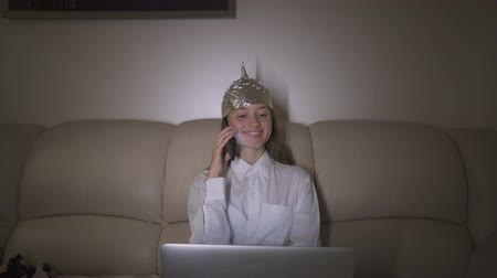ón : Tin Foil Hat protects woman`s brain from 5G waves, internet, electromagnetic fields, mind control. Girl speaks on the phone.