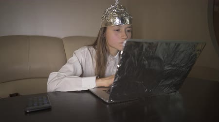 elmélet : Young woman in Tin Foil Hat typing message on keyboard, laptop with foil. Foil hat shields her from 5G waves, internet, electromagnetic fields, mind control and mind reading, illuminati. Stock mozgókép