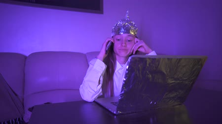 герои : Young woman in Tin Foil Hat speaks expressively on the phone, smile. Foil hat shields her from 5G waves, electromagnetic fields, mind control, mind reading, global conspiracy, illuminati.