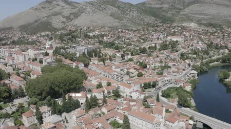 hegyvidéki : Aerial footage of Trebinje Old Town in mountain landscape near Trebisnjica river, Bosnia and Herzegovina. Summer sunny day.