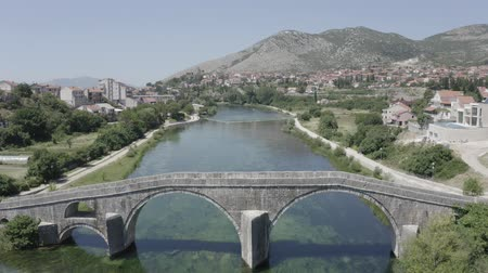 bosnia and herzegovina : Aerial view of Arslanagic`s bridge on Trebisnjica river in Trebinje Old Town. Bosnia and Herzegovina. Summer sunny day, Turquoise water, mountains, trees, blue sky, small houses. Village landscape.