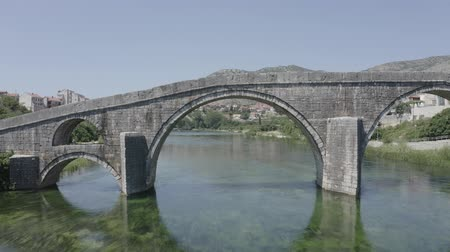 herzegovina : Aerial footage of Arslanagic`s bridge on Trebisnjica river, Trebinje Old Town. Drone flies under bridge, glides above clear water surface. Bosnia and Herzegovina. Sunny summer day.