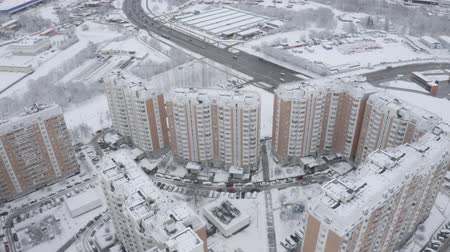 elite : Aerial footage of residential complex, sleeping area in winter. Modern large panel houses, high buildings, kinder yards, sport ground and highway with going cars. Cars paarked near houses. Novo-Peredelkino, Moscow, Russia.