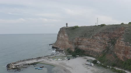 bulgarien : Aerial footage of Bolata Cove on Black sea, Bulgaria. Sand beach on the sea shore near cape Kaliakra. Cliffs, stones, foaming waves, colorful boats. Drone goes up.