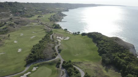 golfjátékos : Aerial footage of Thracian Cliffs golf and beach resort. Beautiful landscape with green hills, meadows, golf course, pond, road, hotels, trees near the shore of Black sea, Bulgaria. Summer sunny day.